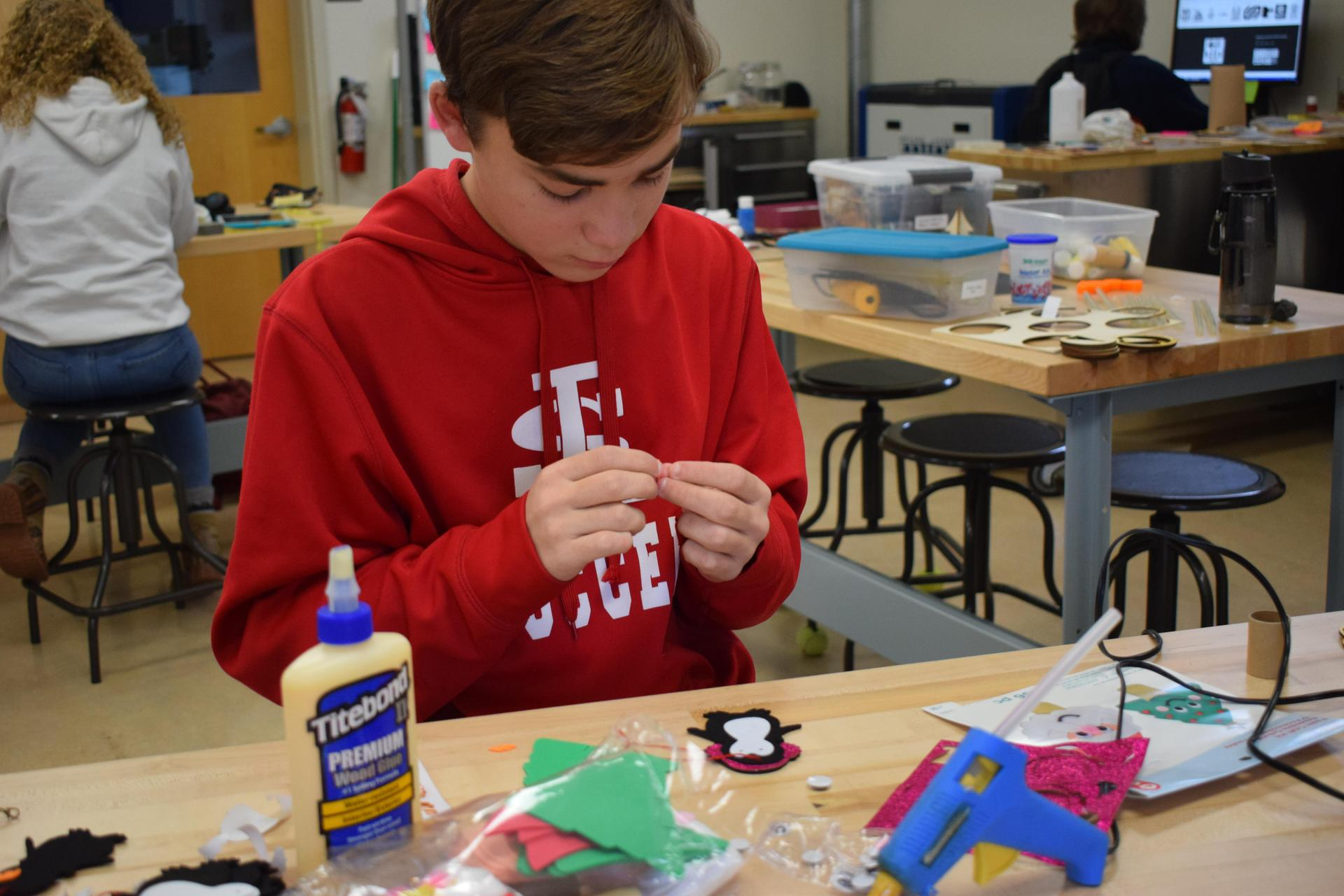 Student looking at his hands while he puts something together. He is wearing a red sweatshirt and jeans and sitting in a classroom.