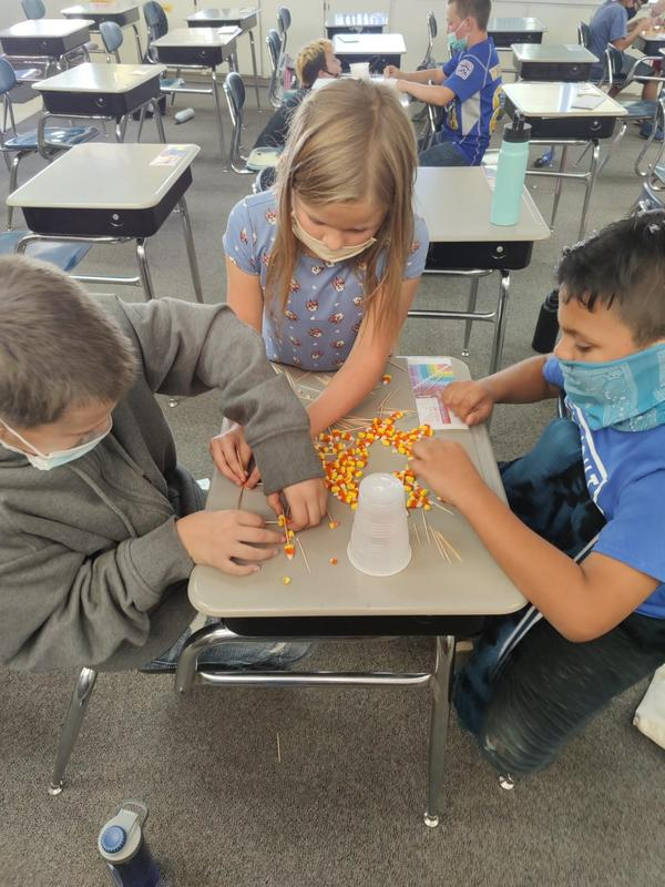Students making a candy corn tower