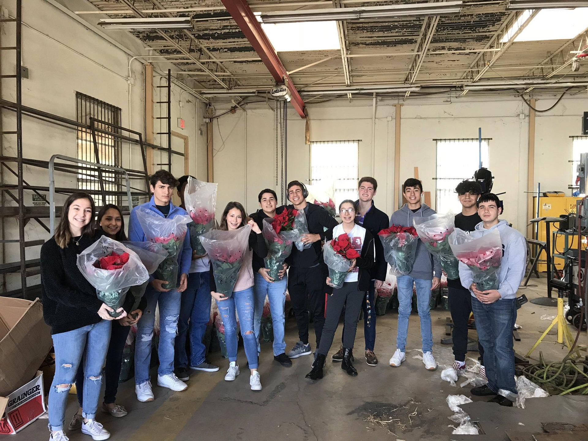 students holding bouquets of roses