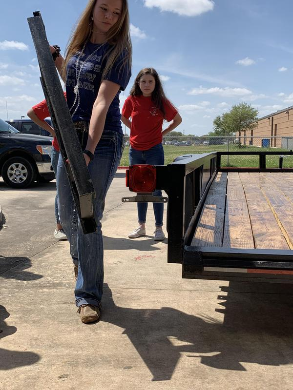 a girl carrying a ramp to the back of the trailer