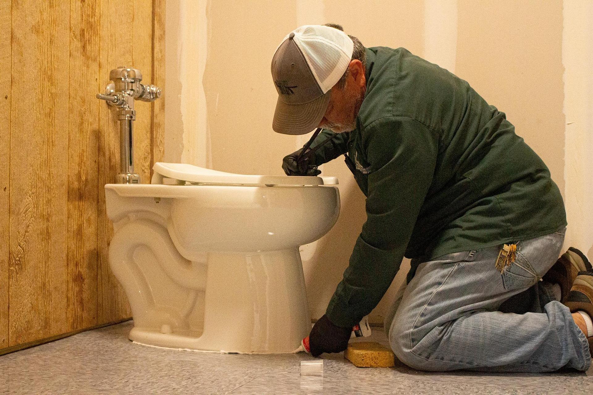 man installing toilet
