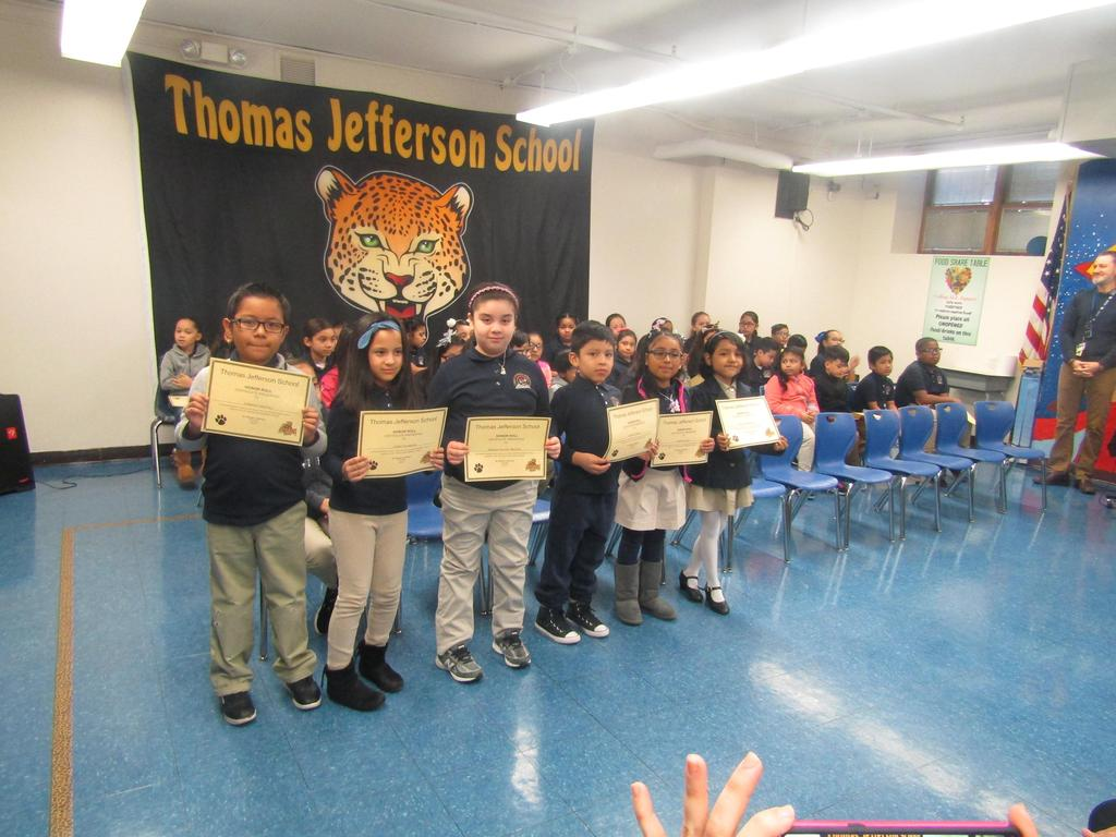 third group of children holding up their honor roll certificates