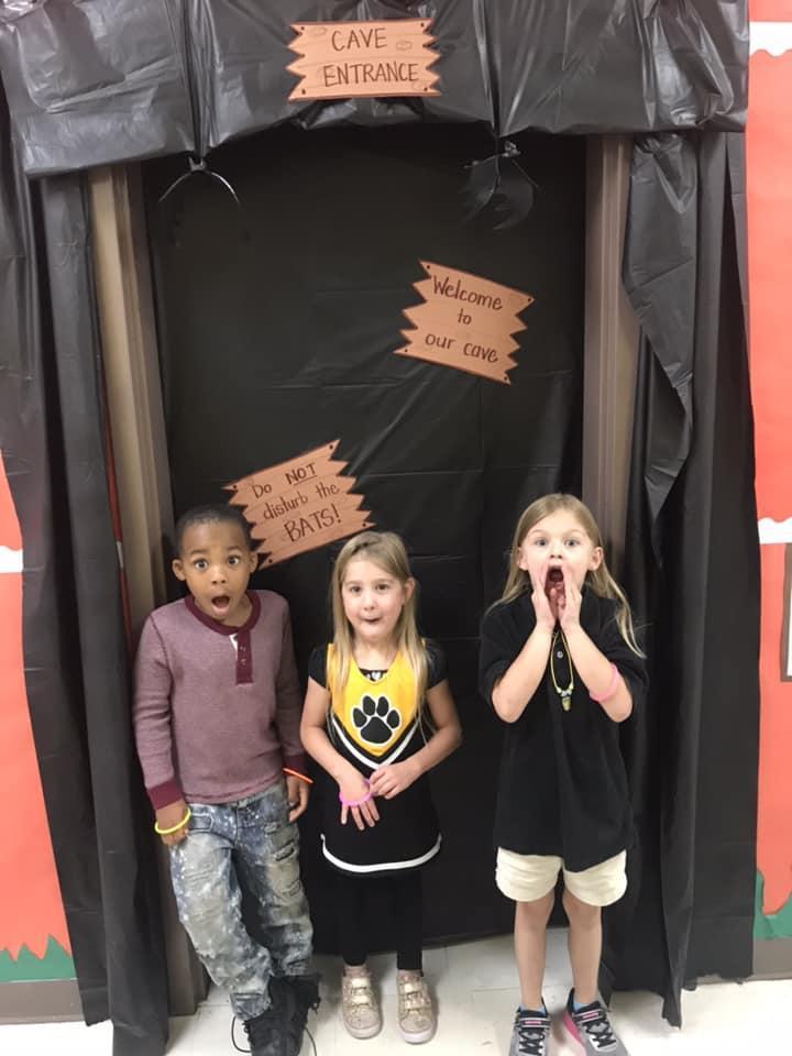 Students standing beside decorated door