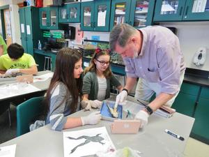Sixth-grade teacher Shaun Davis shows students how to dissect a frog to look at the organs inside.