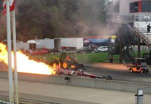 A dragster car in action with fire coming out the back of it.