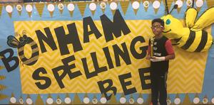 Student in front of spelling bee sign