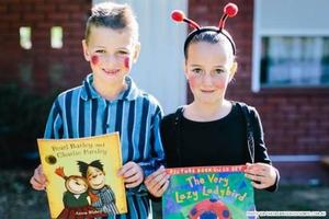 Kids in costumes with books