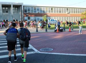Edison Intermediate School crossing guard helps students as they arrive for first day of school.