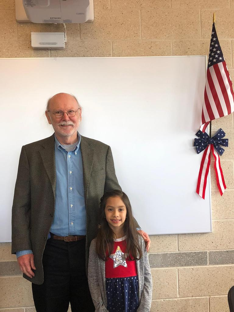 young girl stands with her grandfather vet