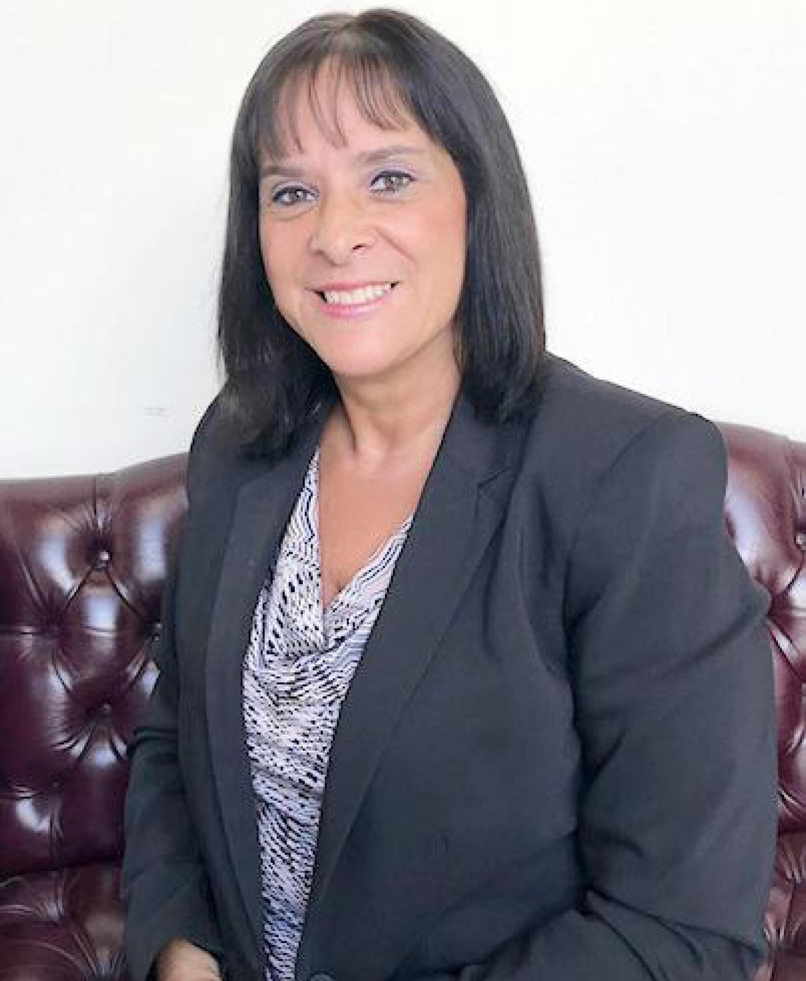 Formal photo, Cynthia Sarnie, sitting in a large leather chair