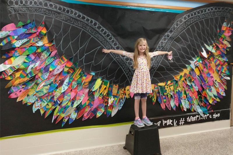 student posing with the mural