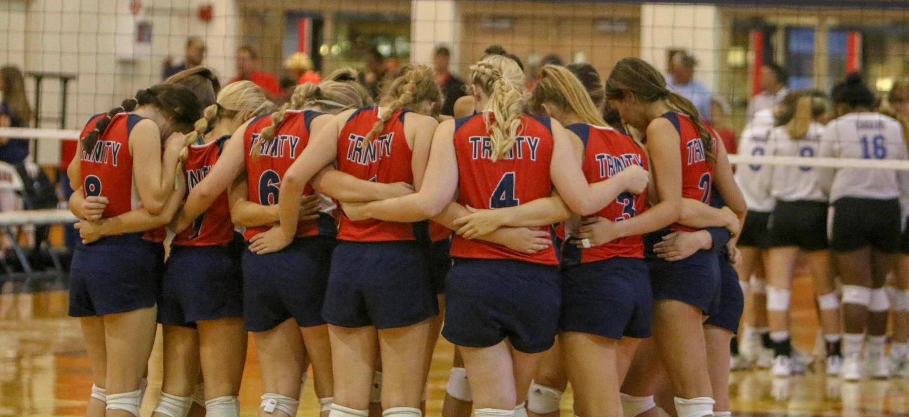 Volleyball team praying before the game.