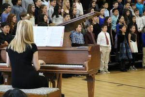 Photo of band director Marisa Minogue on piano as Tamaques Grade 5 chorus sings.