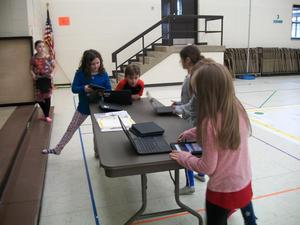 Students use Chromebooks and iPads to learn information about the giant NC map.
