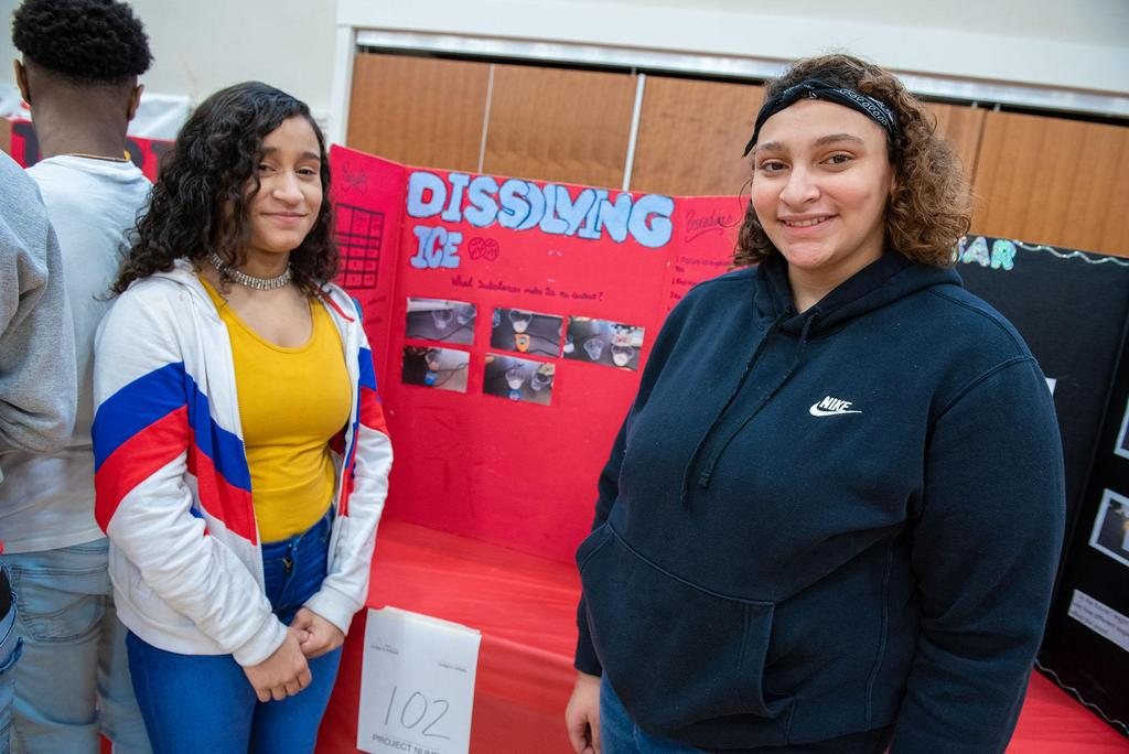 Two students stand in front of their project called Dissolving Ice