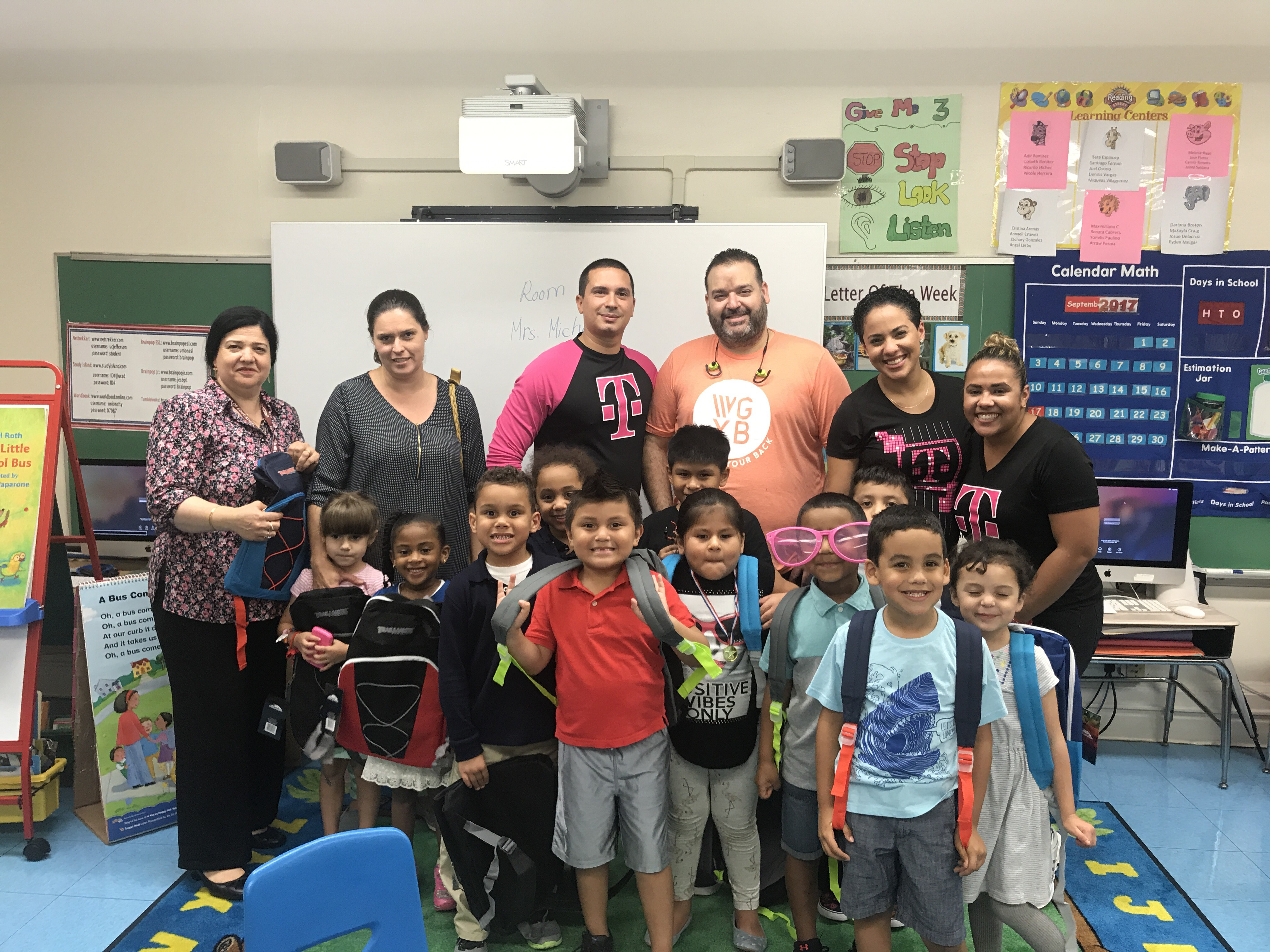 Tmobile representatives with students who received free backpacks