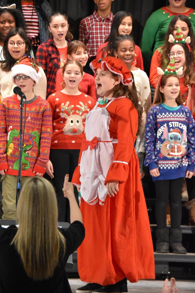 A girl dressed as Mrs. Claus sings