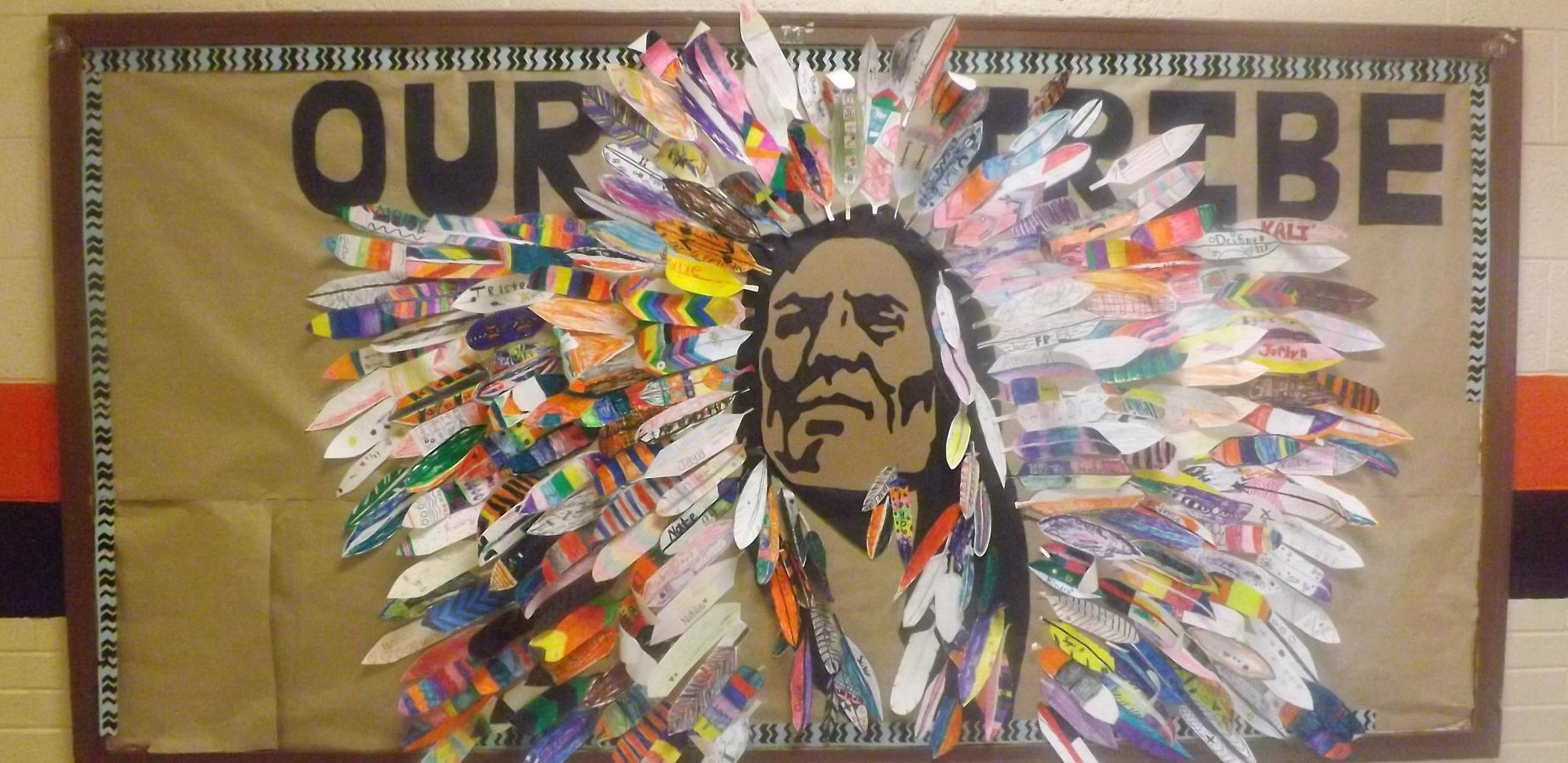 Picture of a bulletin board in DeBusk's main hallway of the Brave mascot. The headdress is made of feathers with children's names on them.