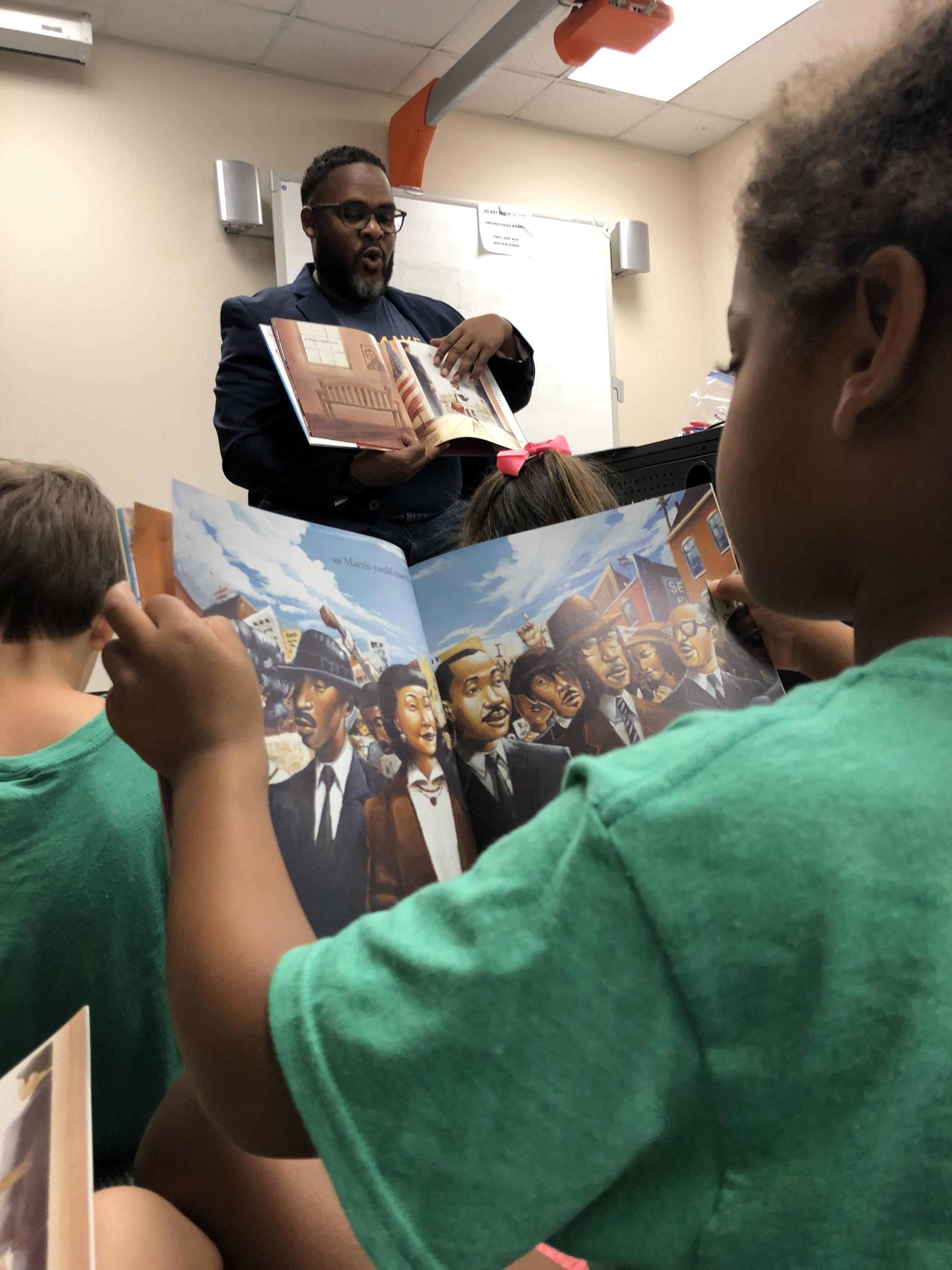 Students listening to a read-aloud given by Julius B. Anthony, one of Atlas' board members.