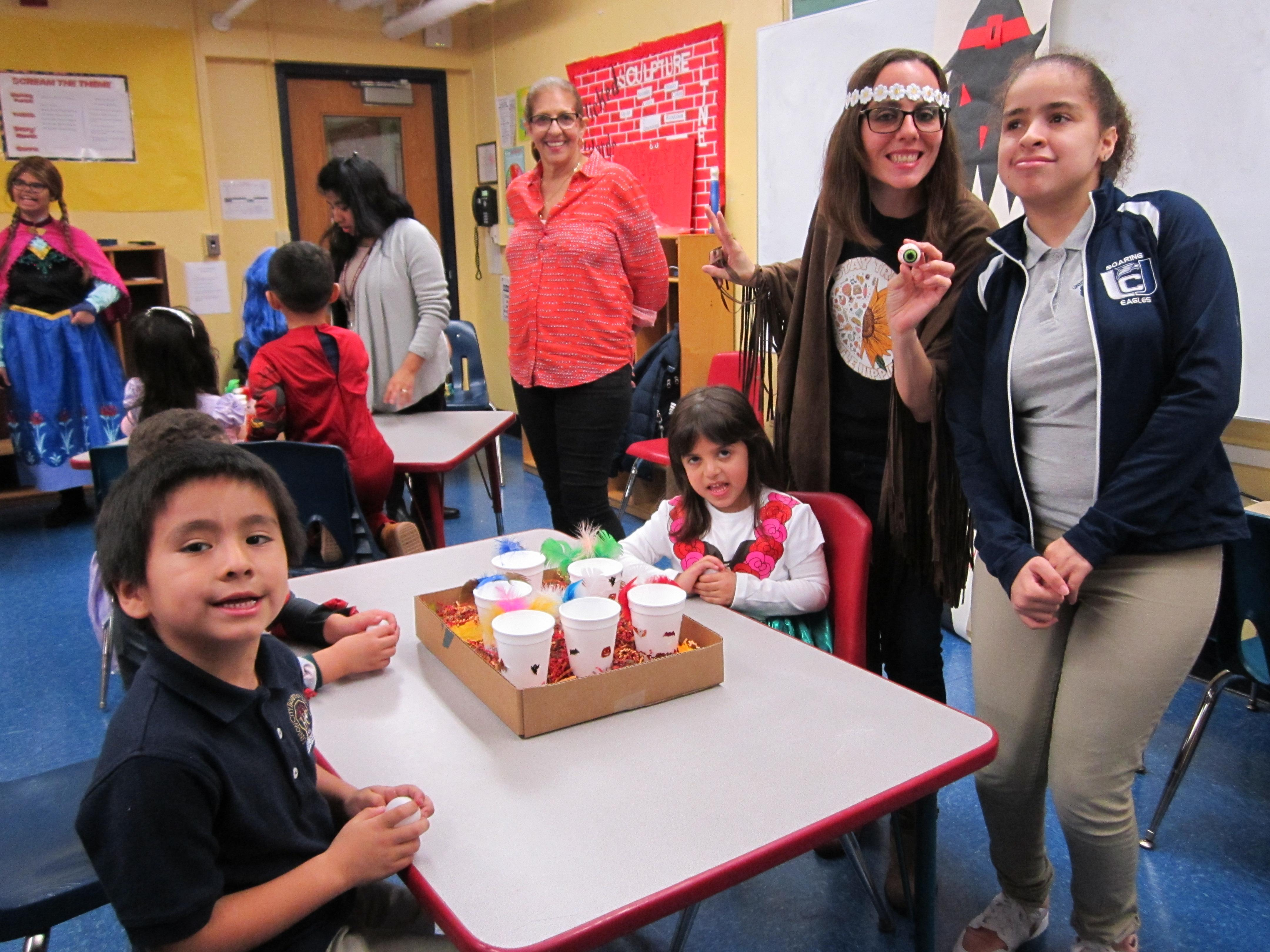 ms. Viera and one her female student holding a fake eyeball playing a dunking game with two kindergarten kids as an aide looks on