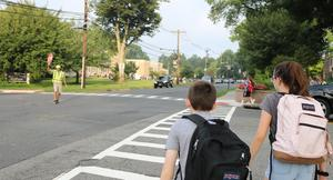 Crossing guard at Roosevelt Intermediate School help students cross street during first week of school.