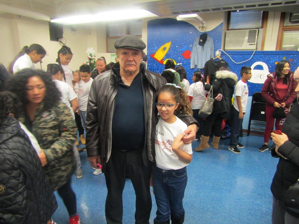 veteran grandpa holding his granddaughter who performed