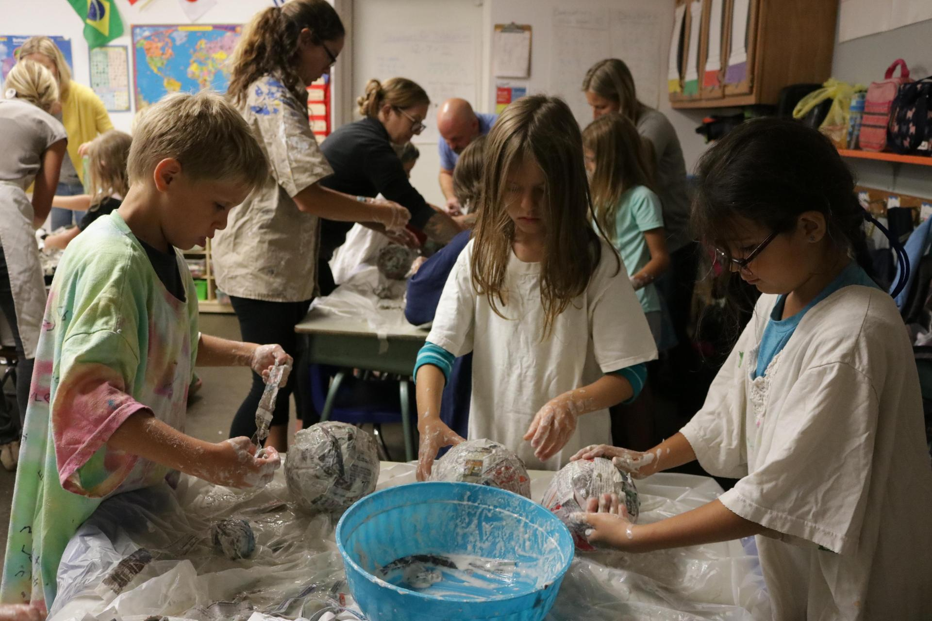 Students work together on a paper mache project