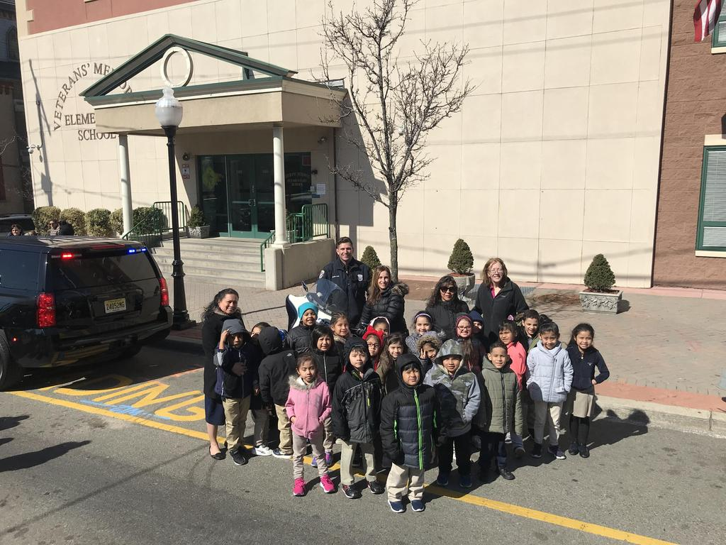 group of children, principal, aides, and officer pose in front of school