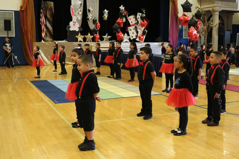 kindergarten classes standing in group in the gym in front of the audience