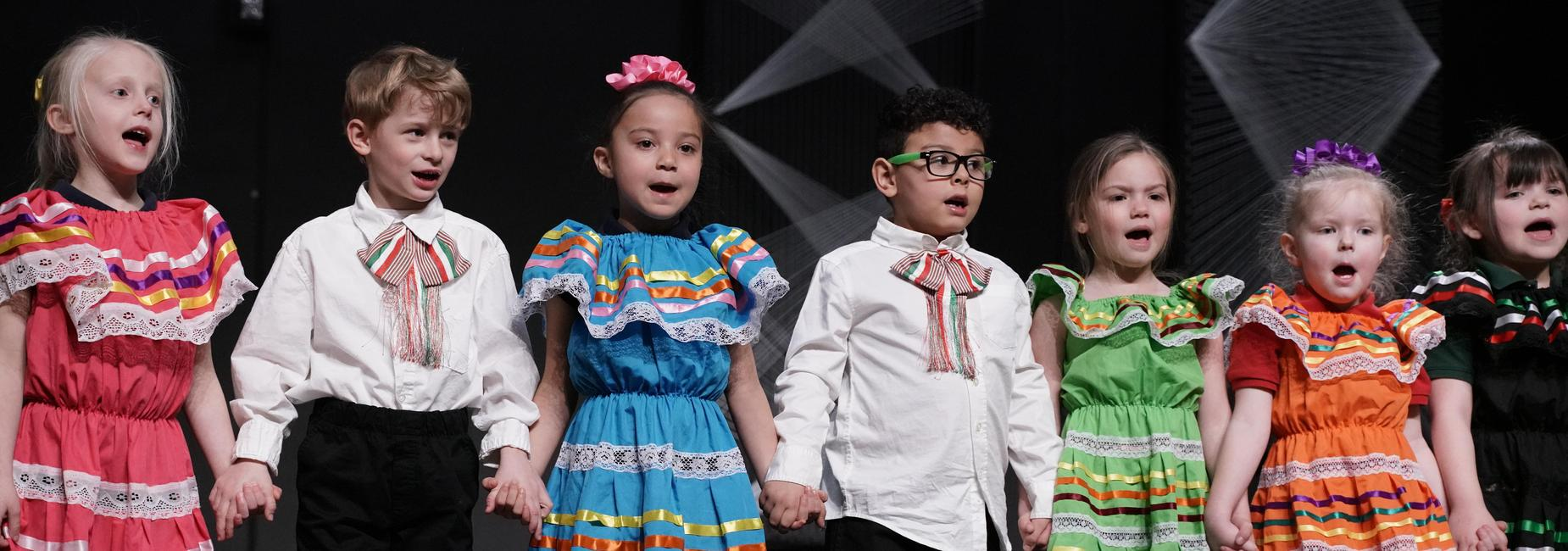 Colorfully dressed students sing at the CILA culture show