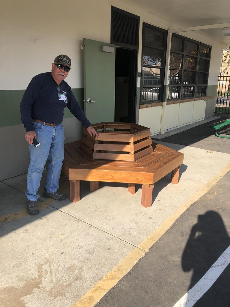 NBCC member stands in front of bench donated year prior