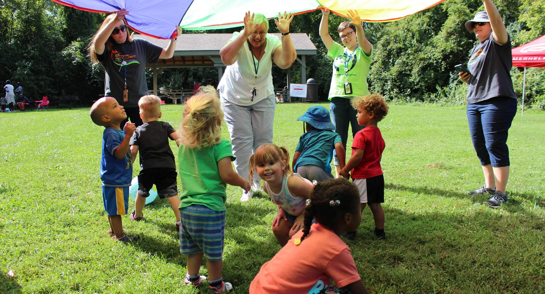 Children in early childhood programs play parachute game outside at the annual family picnic