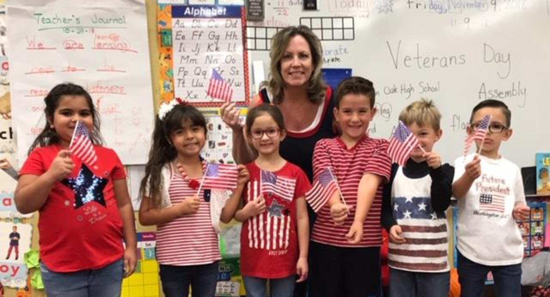 First Grade students waving American flags