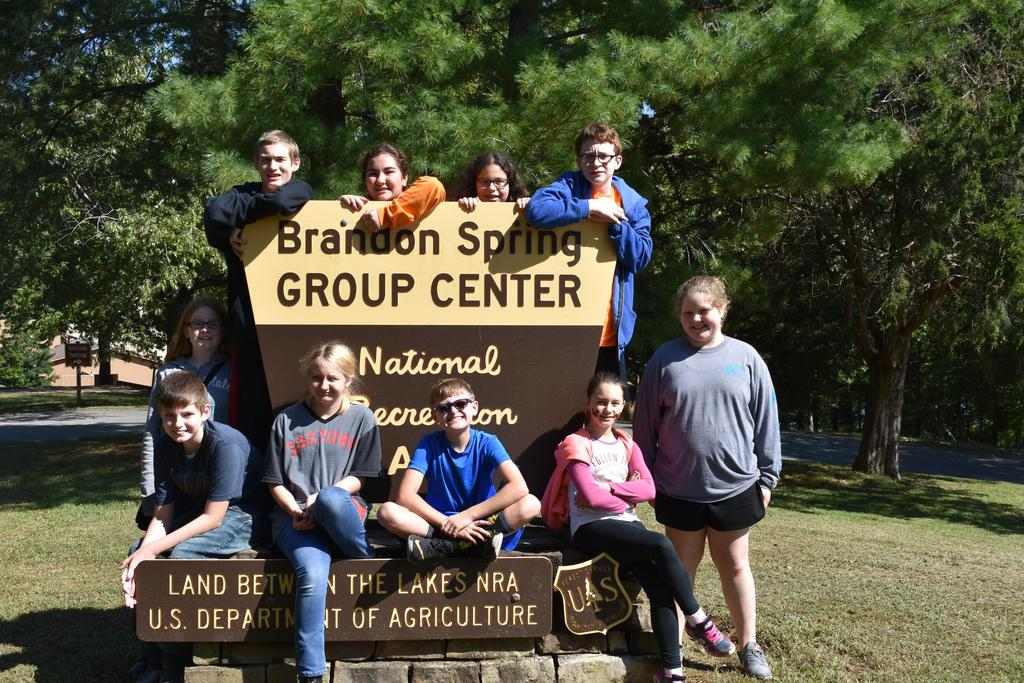 Day group posing in front of the Brandon Springs welcome sign