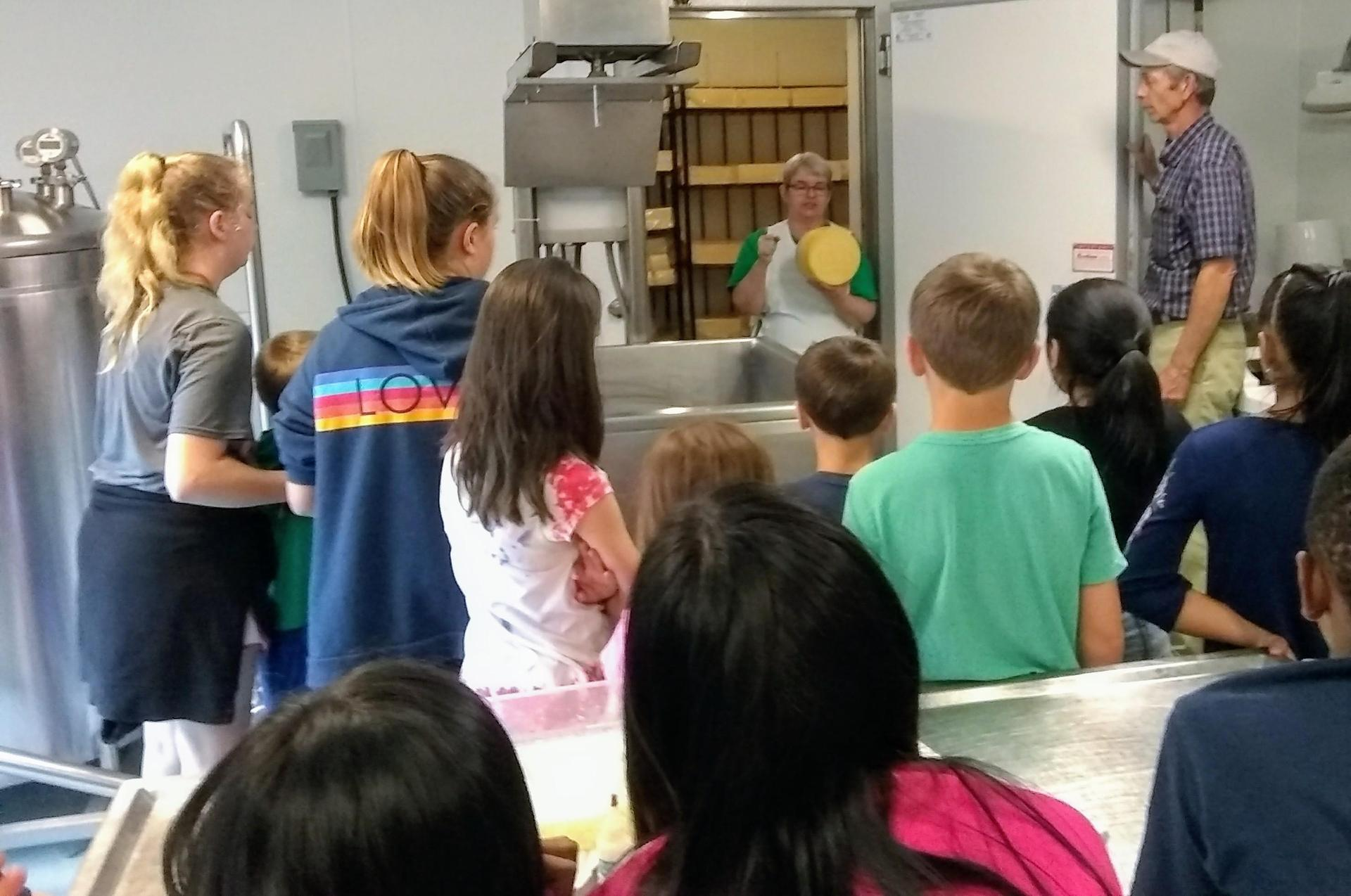 kids listen to the cheesemaker show aging cheese wheels