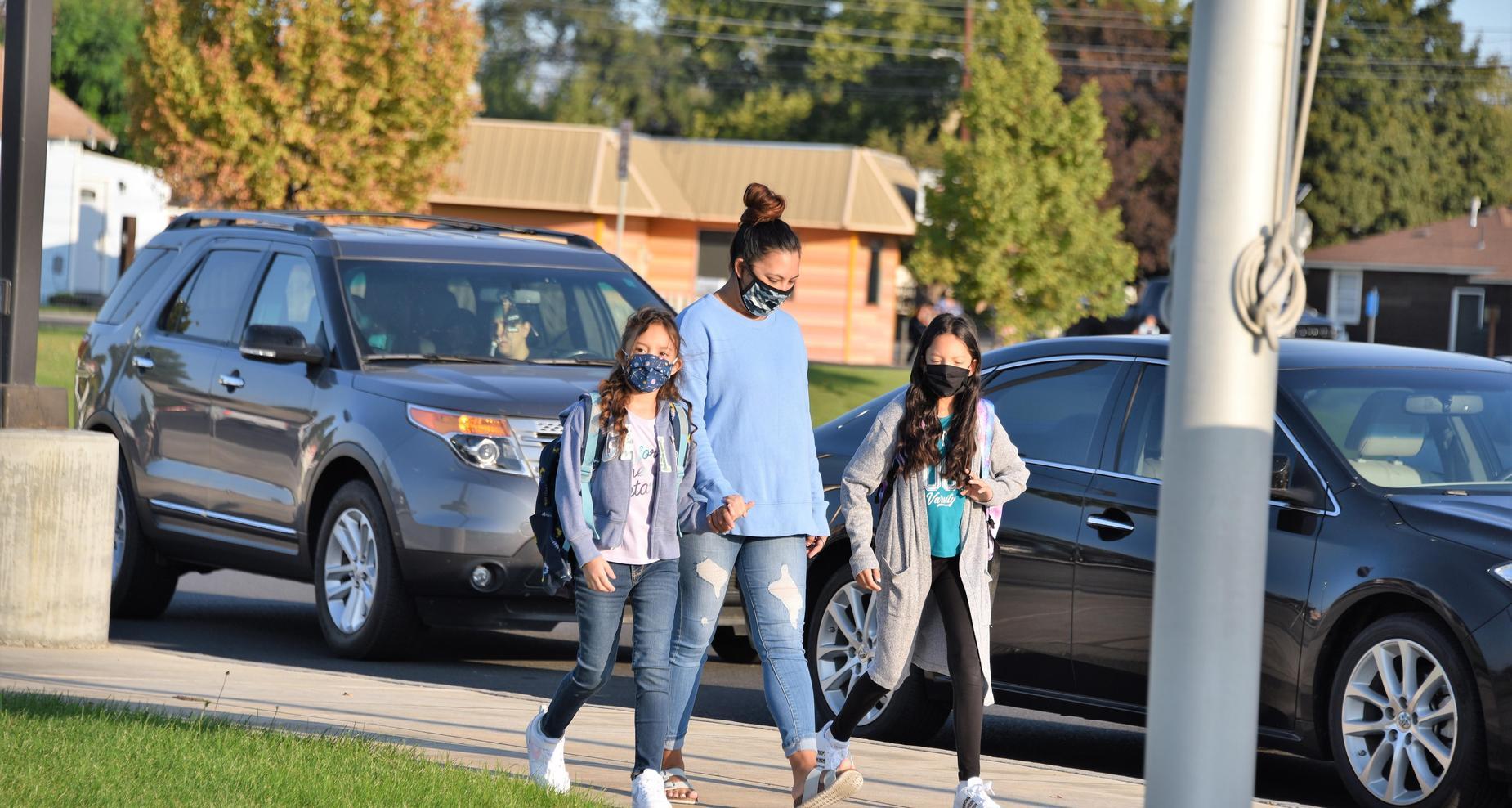 Mom walking her daughters to school.