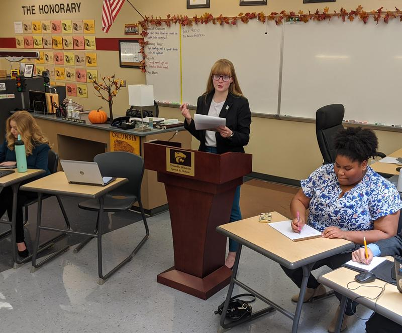 Debater competes at the podium while judges make notes.