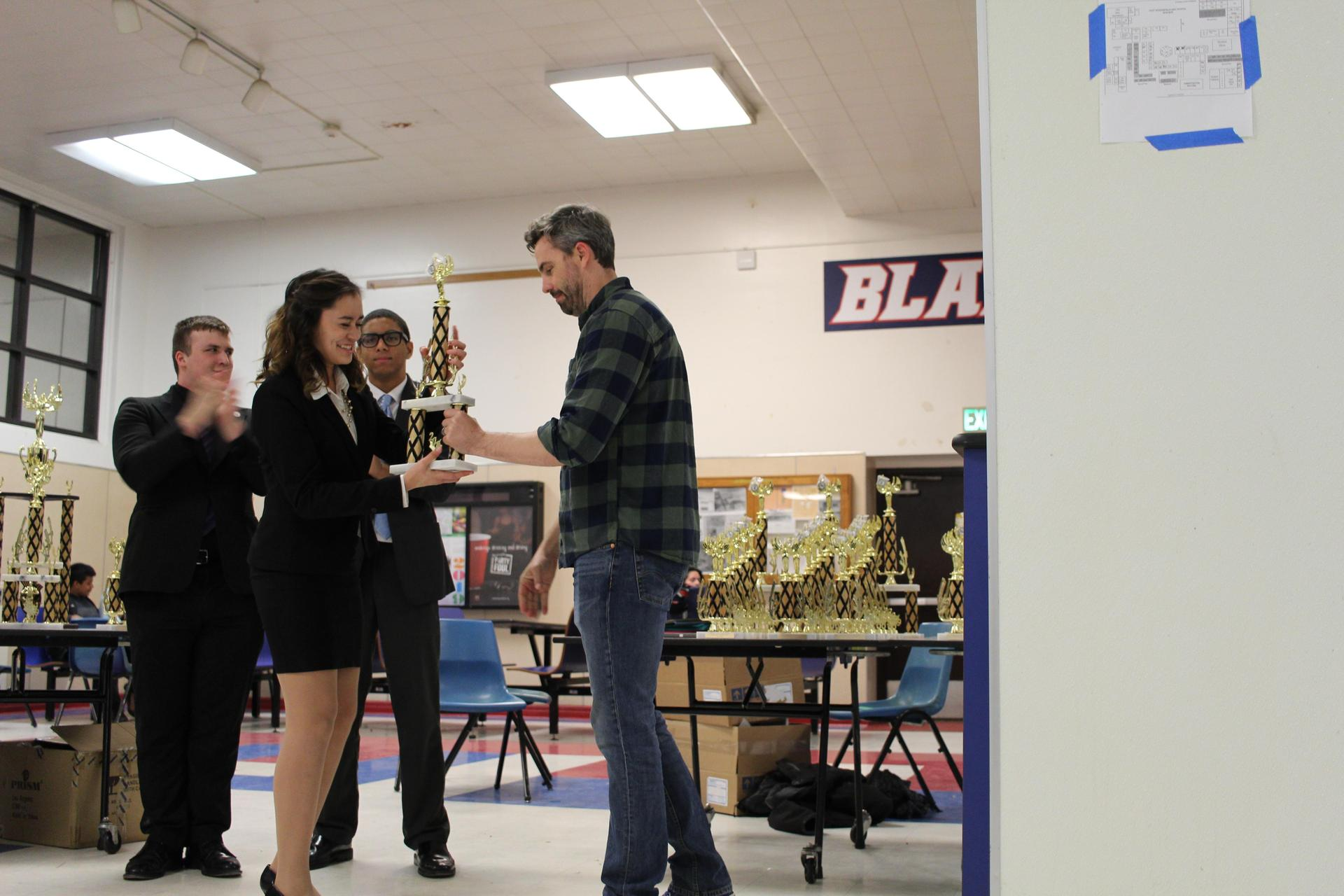 Andrea Jimenez receives the trophy for winning the Speech and Debate Valley Championship for Original Oratory.