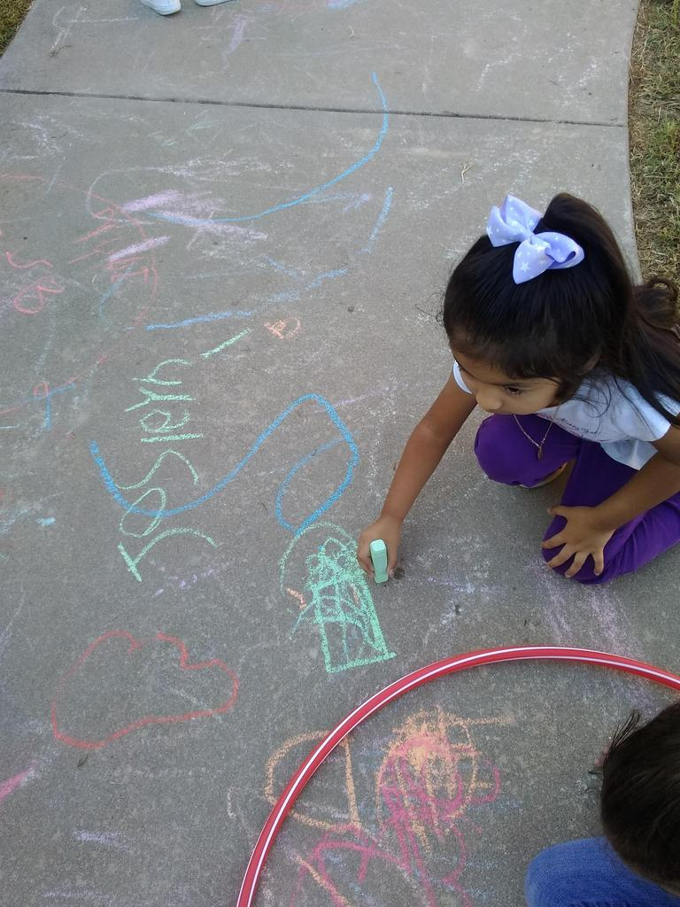 Pre-K student writing/drawing with chalk on the sidewalk outside of school
