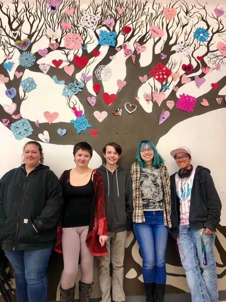 students posing by art mural of tree