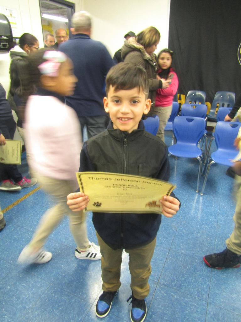 boy proudly showing off his certifcate