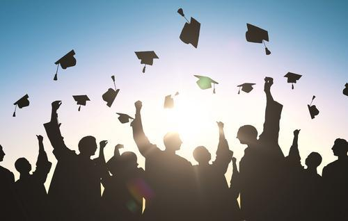 High school graduates throwing their caps into the air.