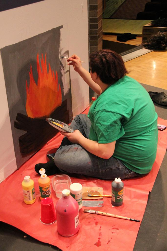 Student painting a picture of a fireplace