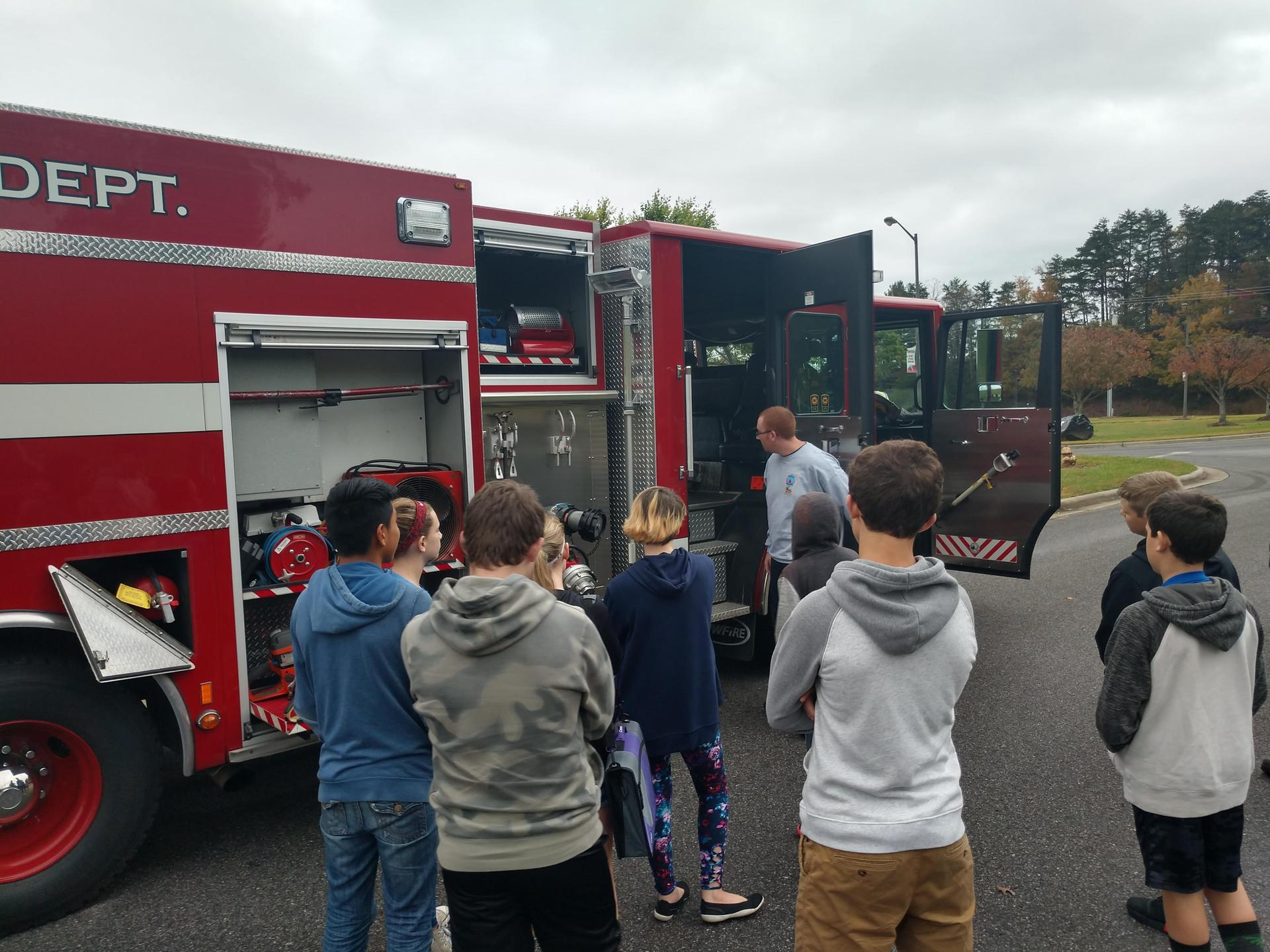 Firemen show off a fire truck during Career Day.