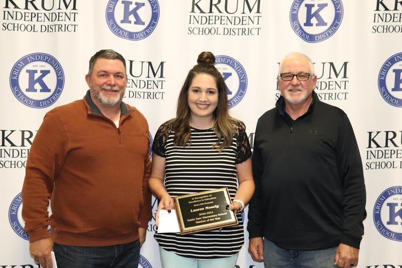 lauren mosely stands with board president eric borchardt and board vp terry knight as they present her with her teacher of the year plaque
