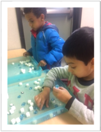 Preschool students working with manipulatives