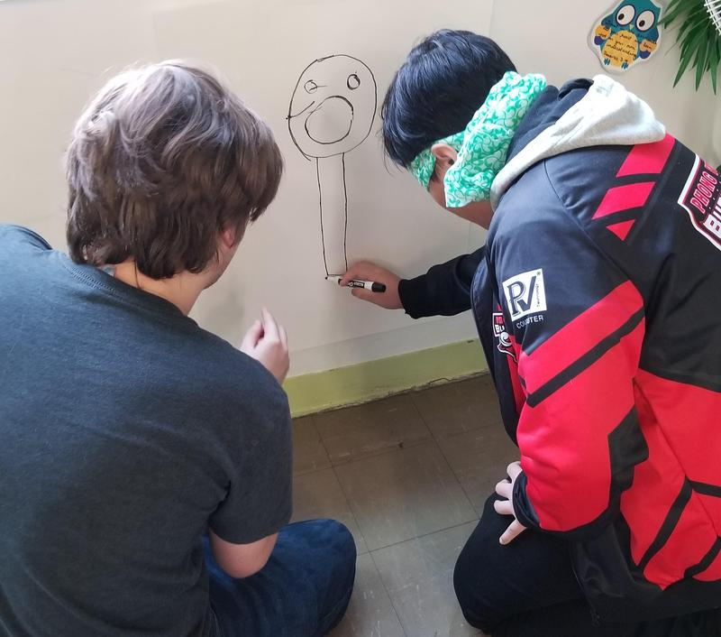 A blindfolded student is receiving directions from another student.
