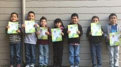Students posing for the camera while holding up their student awards.