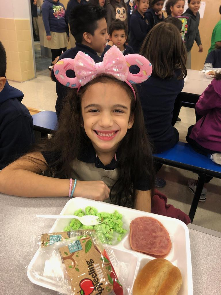 girl smiling as she's eating green eggs and ham