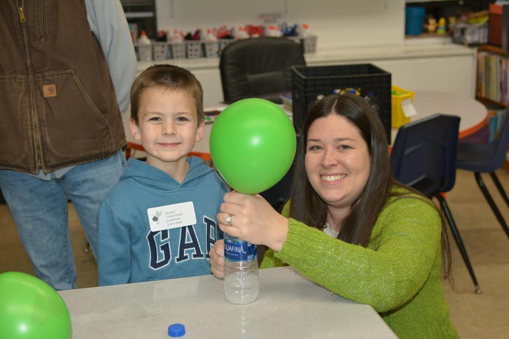 Mrs. Haynes helps a student with science experiment on Grinch night